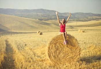 Canva - Woman Sitting on Hay Roll