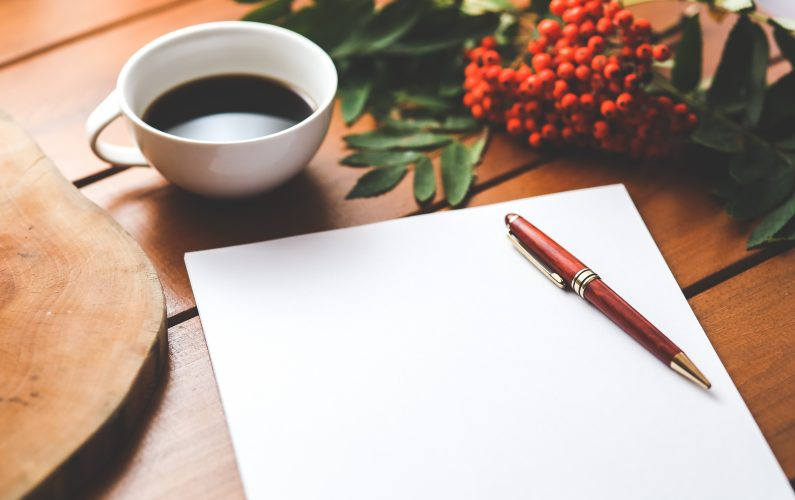 Canva - Blank paper with pen and coffee cup on wood table