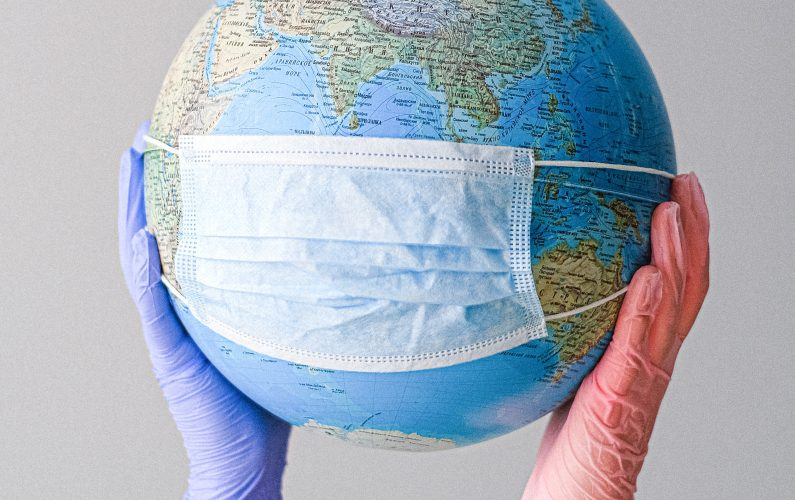 Canva - Hands With Latex Gloves Holding a Globe with a Face Mask